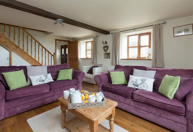 There is a spacious sitting-room with comfortable sofas and a wood-burner effect electric stove in the fireplace.