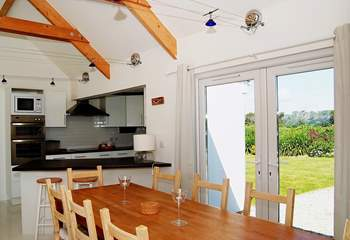 Beside the dining-table, there are patio doors which open out to the front garden.
