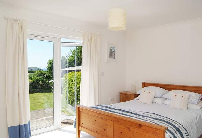 The master bedroom (Bedroom 2) has a king-size bed, an en suite shower-room, and patio doors opening onto the deck in the back garden.