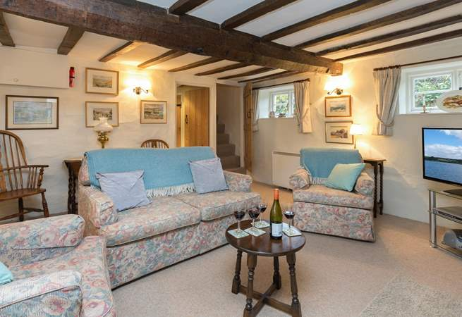 Another view of the sitting-room - plenty of comfy seating. You can glimpse the turning cottage stairs to the bedrooms.