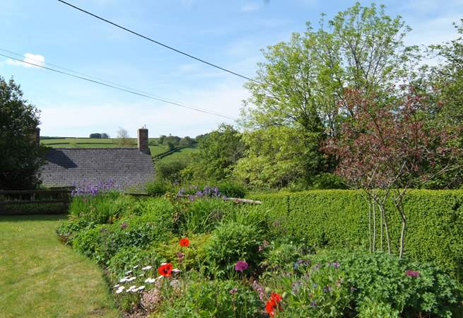 The beautifully looked after garden looks out over the top of the village to the stunning views across the valley.