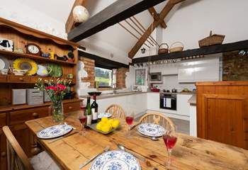There is a farmhouse style dining-table next to the kitchen-area.
