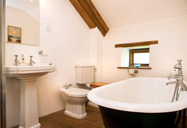 The en suite bathroom has a double-ended roll-top bath with a separate shower cubicle.