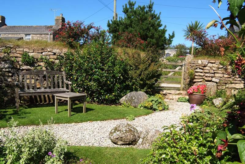 The pretty enclosed back garden with its manicured lawn and attractive flowerbeds.