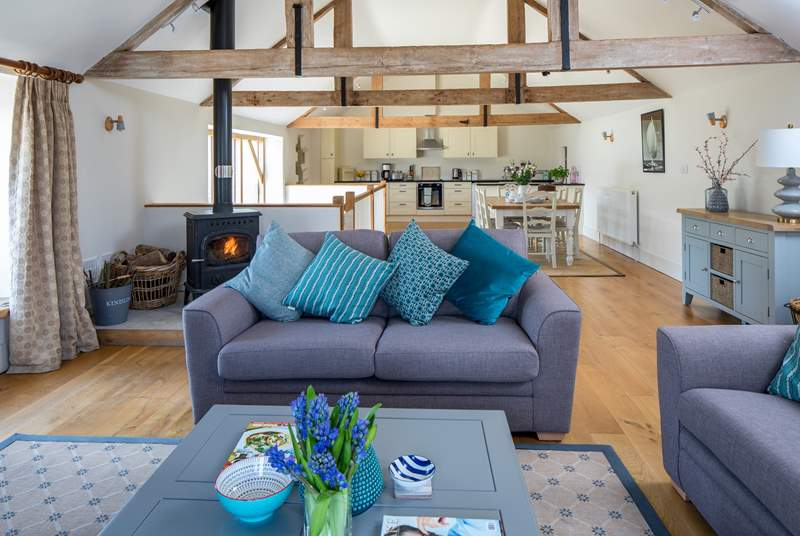 The wonderful open plan first floor living-area with cosy wood-burner, high beams and wooden floor.