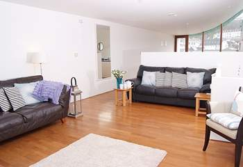 The open plan living space is divided by the kitchen-area, with the dining-table at the far end.