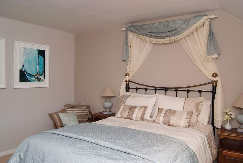 The spacious double bedroom has a king-size bed and gorgeous hand-made soft furnishings.