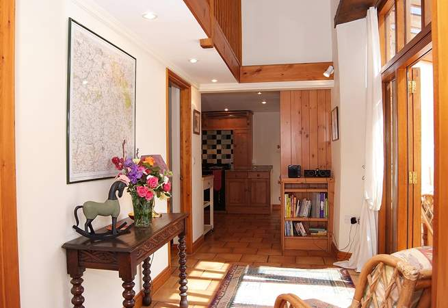 This cottage is very spacious and light.  This is the view from the sitting-room along the corridor to the kitchen, with the sun-room and dining-room to the right.