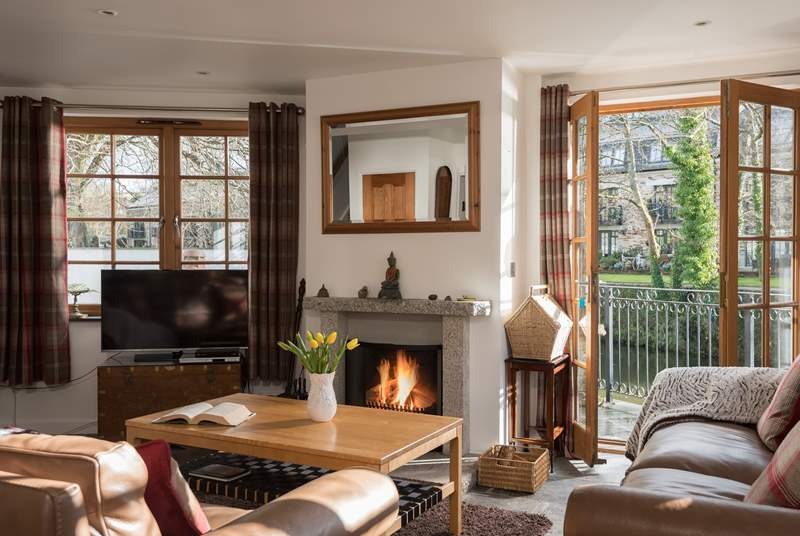 The sitting area of the open-plan living-room has doors out to the waterside terrace.