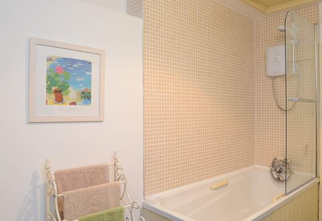 In the bathroom, there is a step up to the bath which is fitted with an electric shower.