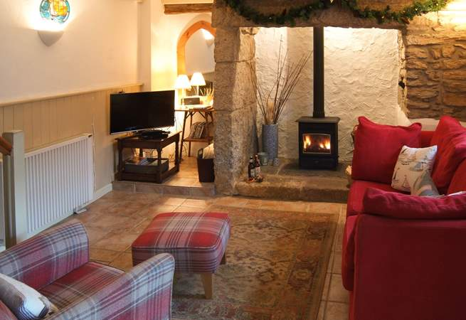 The living-room with comfy chairs and a cosy wood-burner to keep you toasty on those cooler days and evenings.