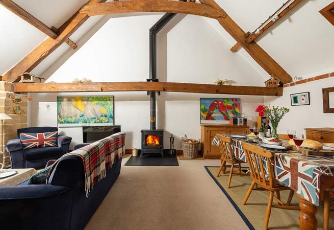 The open plan living/dining-area is separated from the kitchen-area by a low beam.