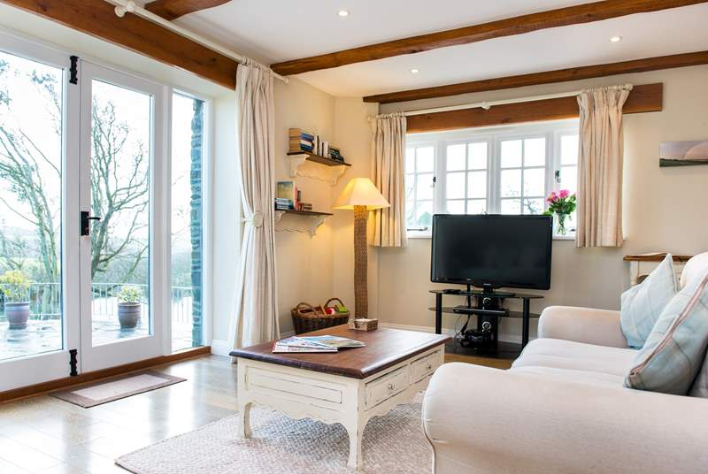 Large patio doors fill the room with light and give direct access to the grounds.