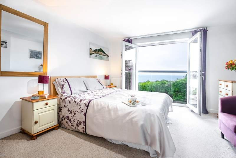 Bedroom 2 has a king-size bed, and double glass doors with a Juliet balcony overlooking the bay.