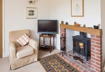 The sitting-room has comfortable sofas and looks out over the garden and open countryside.