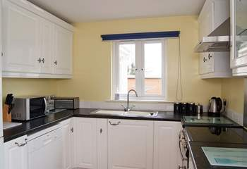 The kitchen is next to the sitting/dining-room and also looks out onto the back garden.