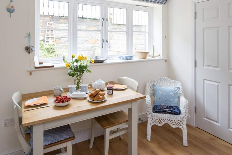 The dining-table sits to one side of the open plan living space, enjoy eating some local produce in this beautiful part of Dorset.