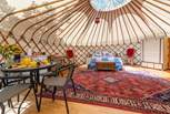 The inside of the main yurt, super spacious and complete with a double bed and dining-area.