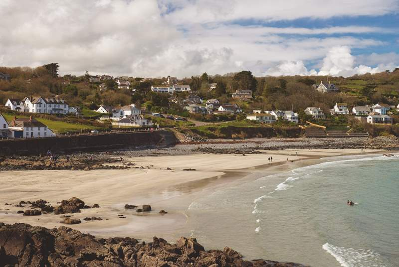 The crescent shaped beach at low tide is sandy and perfect for dipping your toes and building sand castles.