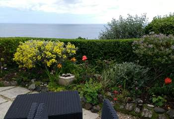 Colourful plants and flowers can be found on the patio. There are the stunning sea views.