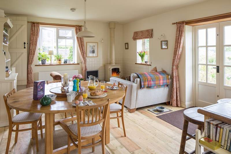 The cottage has a lovely welcoming open plan living-area. There is a wood-burner in one cosy corner and French windows to the garden.