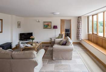 The spacious sitting-room has plenty of comfortable seating. Windows all along one wall face the farm - a great viewing gallery.