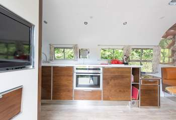 A fully equipped kitchen including dishwasher, oven and induction hob.