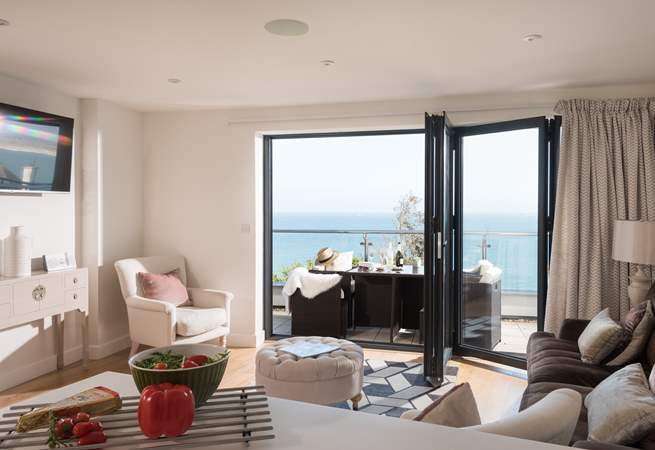 The bi-fold doors open wide, to allow the outside in.