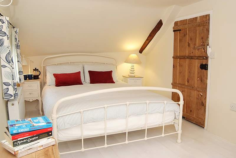 The master bedroom, as with the other bedrooms, has painted floorboards and original cottage doors.
