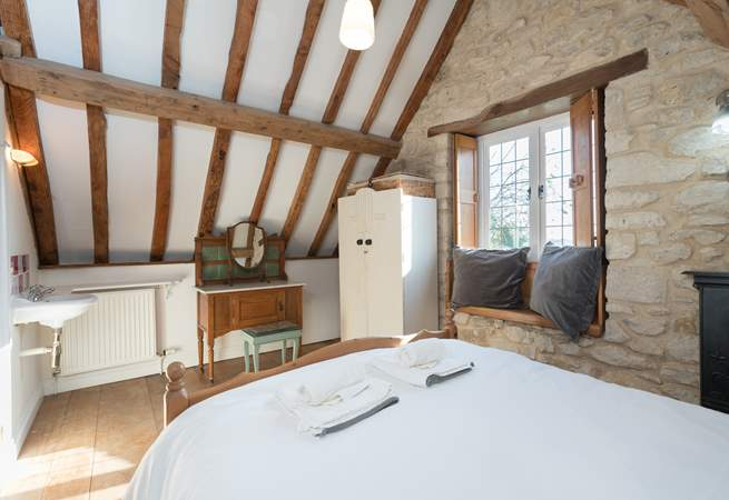 The bedroom has lovely exposed stone walls and a tall beamed ceiling.
