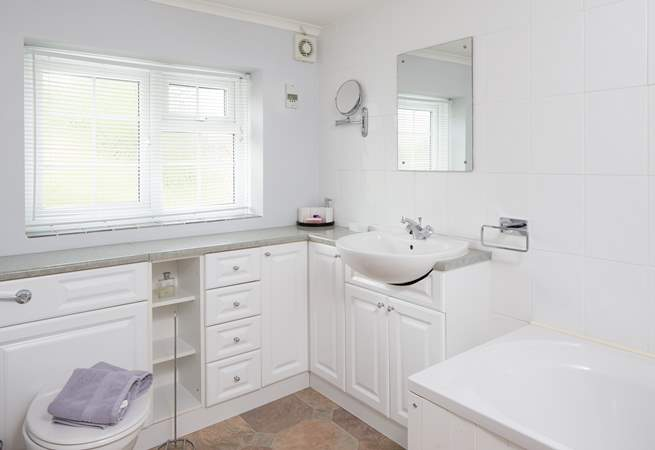 The bathroom is light and bright with a fitted shower over the bath.