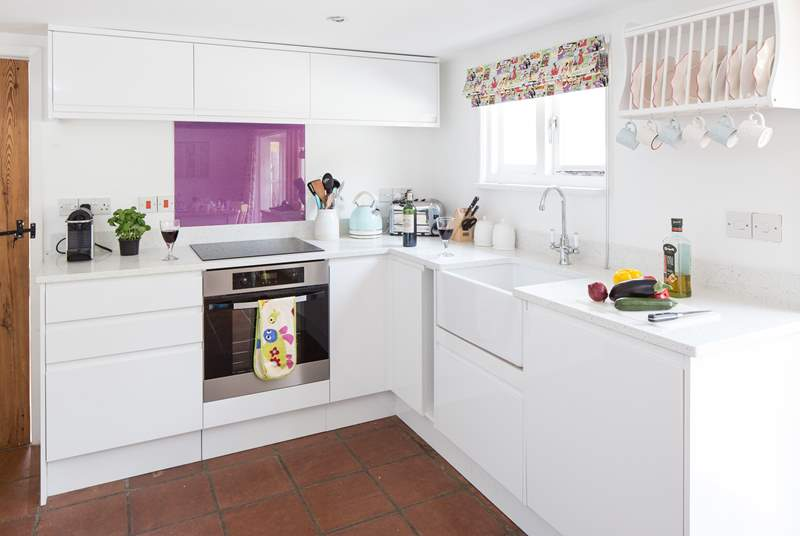 The crisp white kitchen has an induction hob, butler sink, fitted dishwasher and is fully equipped to create a delicious meal.