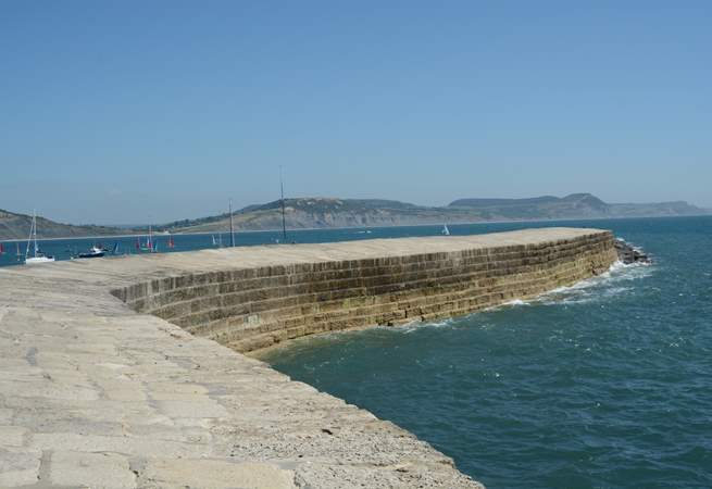 The famous Cobb at Lyme Regis, with spectacular Jurassic coastline behind.