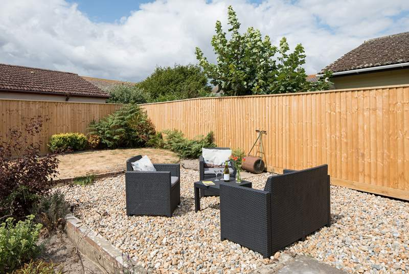 The back garden is fully enclosed with comfy garden seating in addition to a table and chairs.