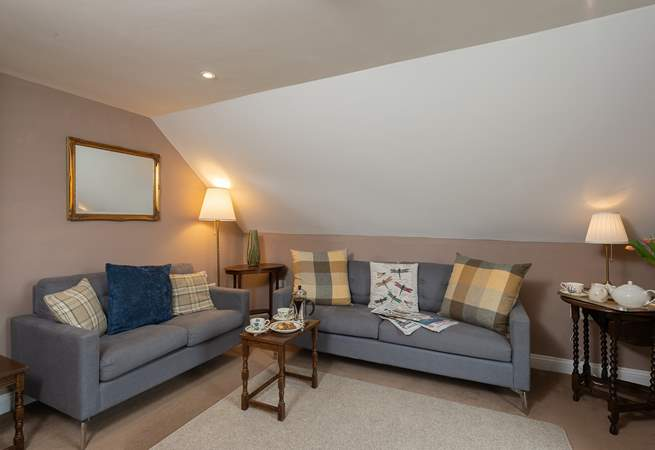 The cosy first floor sitting-oom has two comfortable sofas and wonderful views.