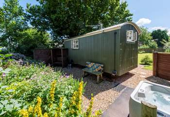 The hot tub is positioned in a private spot to the side of the hut but fully screen fenced for privacy.