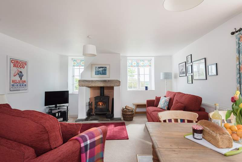 The welcoming living-room with sitting and dining area and a warming wood-burner.