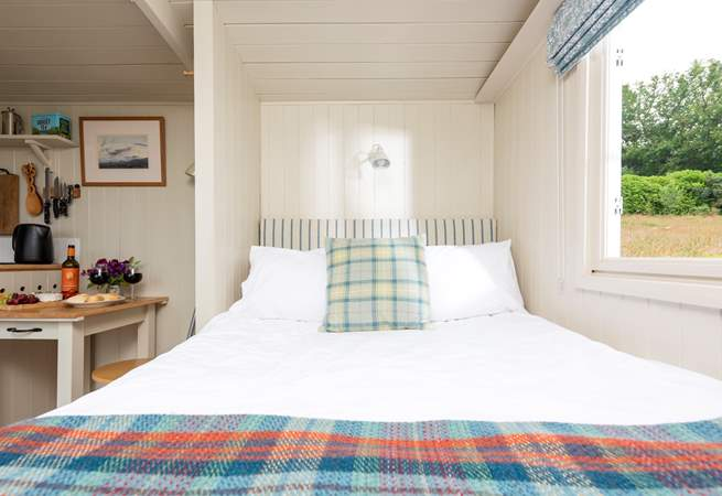 The comfy double bed is tucked away at one end of the hut.