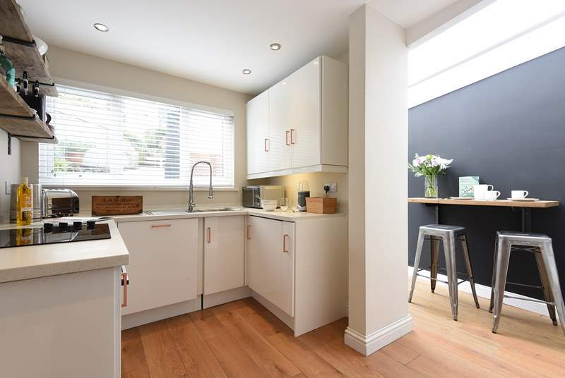 The kitchen/diner is compact but ideal for preparing light meals, and there's a small breakfast-bar.