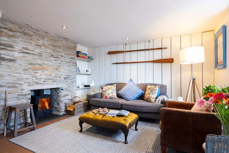 The sitting-room has reclaimed wooden wall panelling and an original stone fireplace with a cosy woodburner.