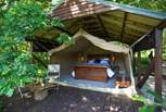 The safari tent is tucked under a magnificent oak tree and has a wooden deck to the front.