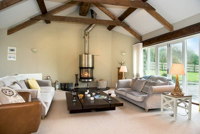 The large sitting room has plenty of space for everyone to relax and the wood-burner takes centre stage