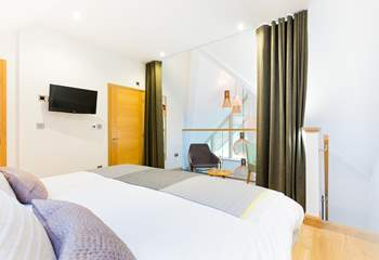 The galleried master bedroom on the top floor overlooks the living space on the first floor. There is a lovely dressing-room next door and an en suite shower-room.