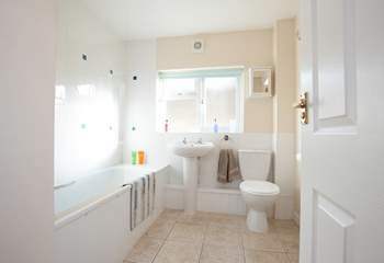 The bright modern bathroom features a shower over the bath.