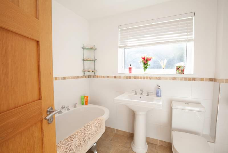 A bright family bathroom on the lower ground floor features a claw-foot bath.