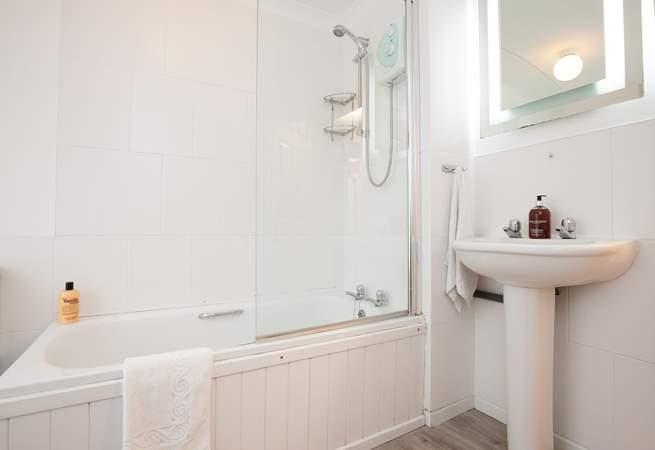 The modern bathroom features a shower over a bathtub.