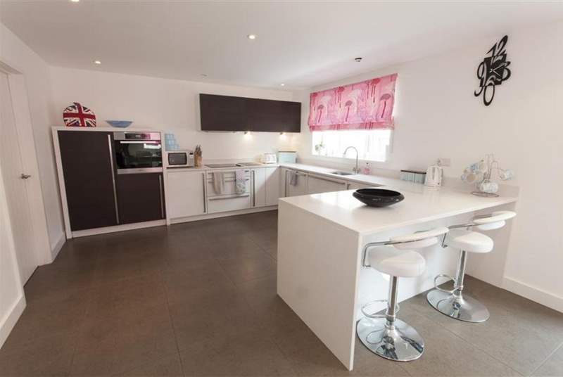 The contemporary kitchen benefits from a breakfast-bar and is fully equipped.