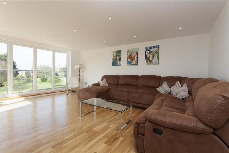 The spacious sitting-room, with generous seating, has doors leading to a large decked balcony.