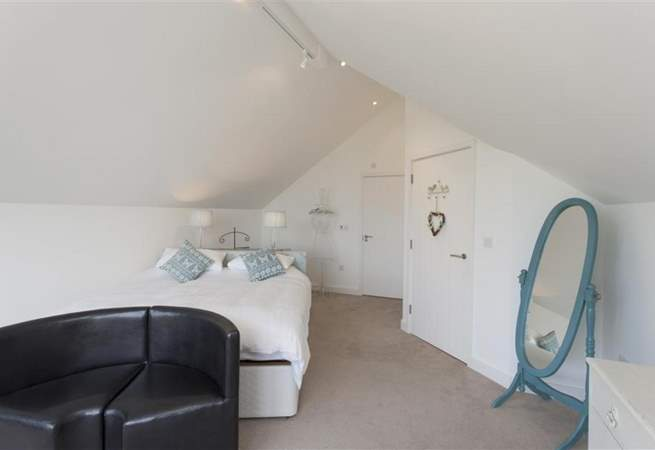 The master bedroom is spacious, with a sofa to sink into whilst you enjoy the views from the large window facing the sea.