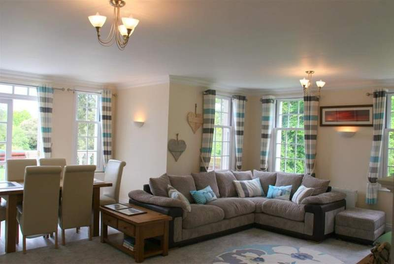 The comfortable living and dining area enjoys lovely views across the leafy grounds.